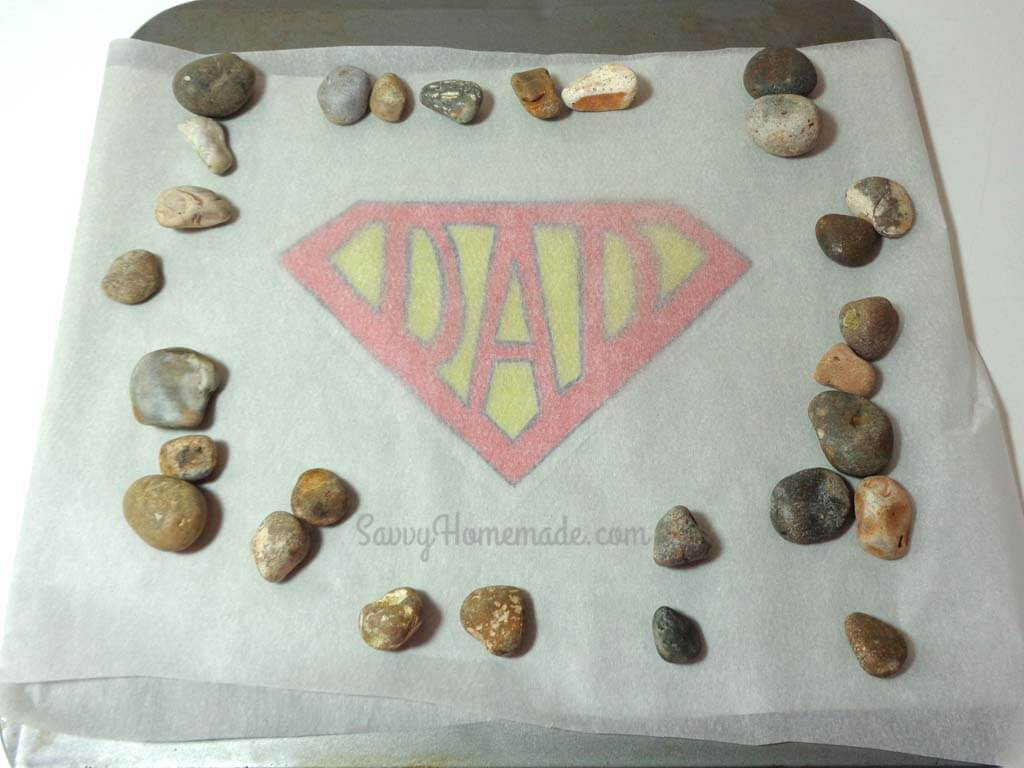 weight shrinky dink down with a few stones or pebbles