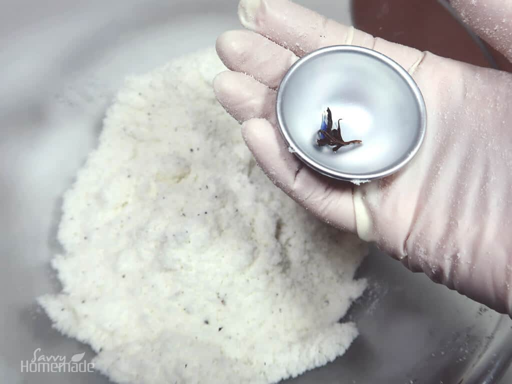 make your own bath bombs step 5b: Put some of the tea in the base of the bath bomb mould.