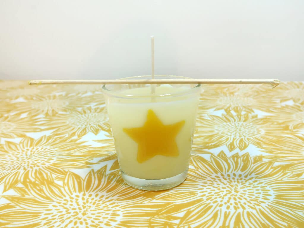 Step 8: Pour your fragranced soy wax into the container with your wick and inbeds, use a bamboo stick to stabilize the wick