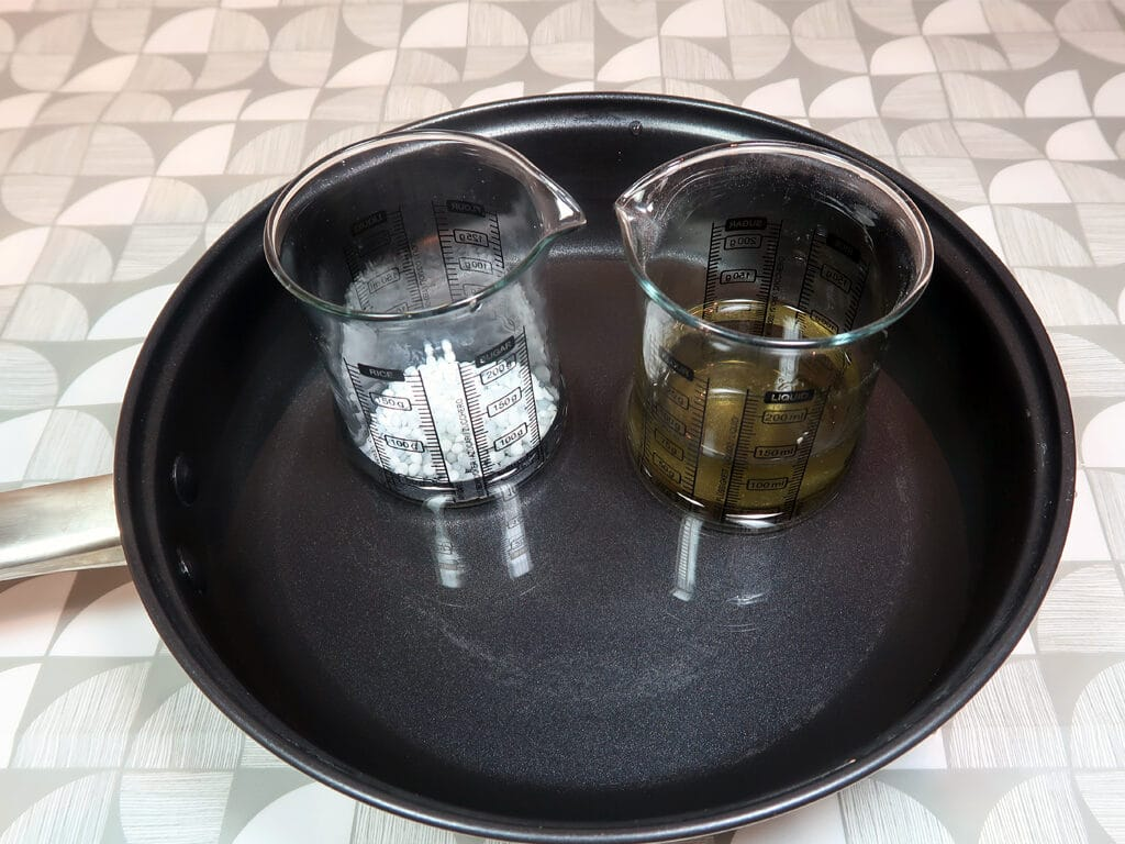 Step 3: Place both beakers into a water bath and heat gently until the wax has melted