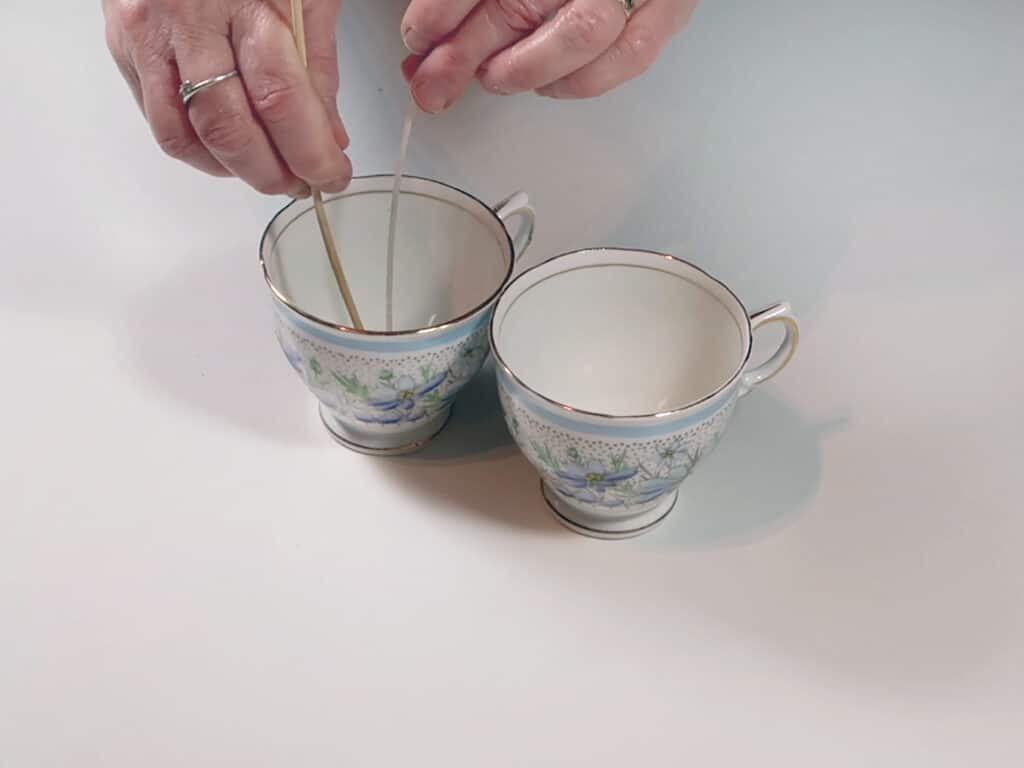 A woman wicks two teacups in prep for pouring candle wax
