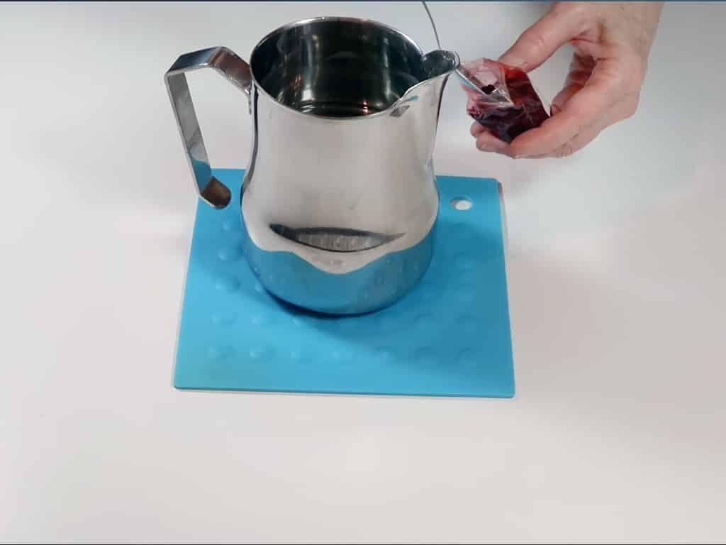 Candle dye being added to freshly melted wax
