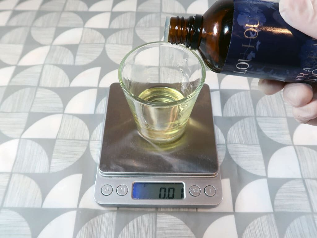 A woman weighs fragrance oil