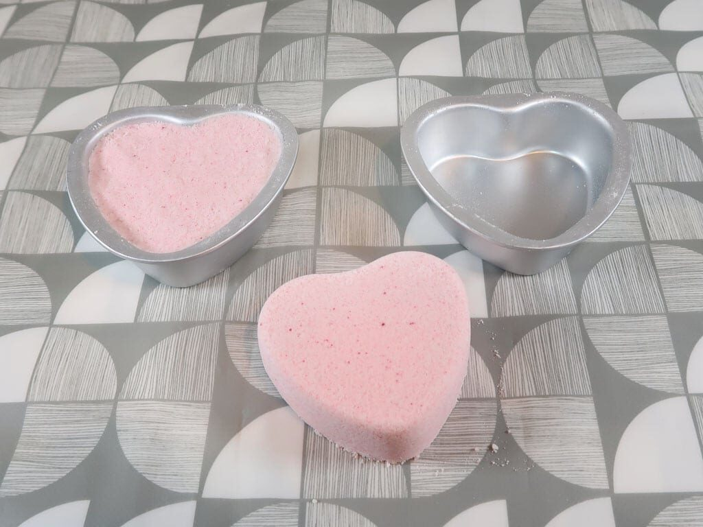Two bath bombs, one in it's mold and the other has been removed from it's mold