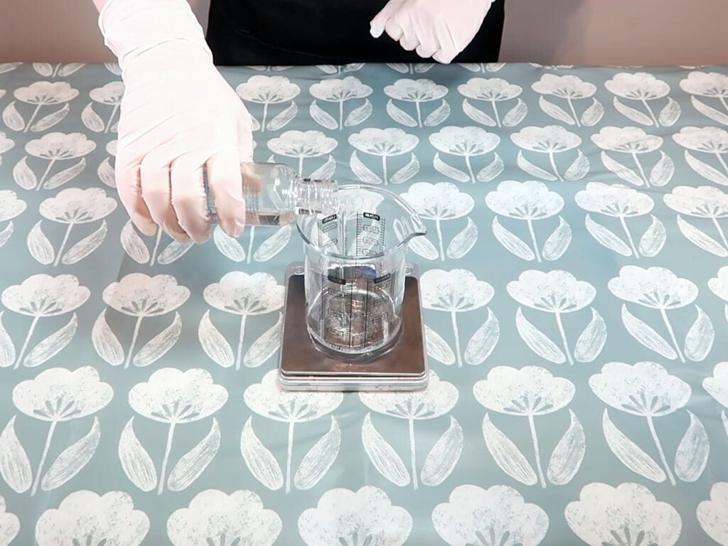 Hydrosol being added to a heatproof, pyrex beaker sitting on a set of digital weighing scales