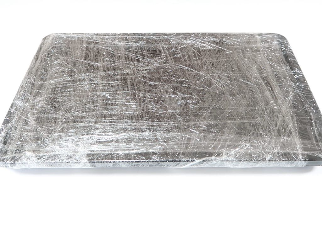 Two baking trays wrapped in plastic wrap