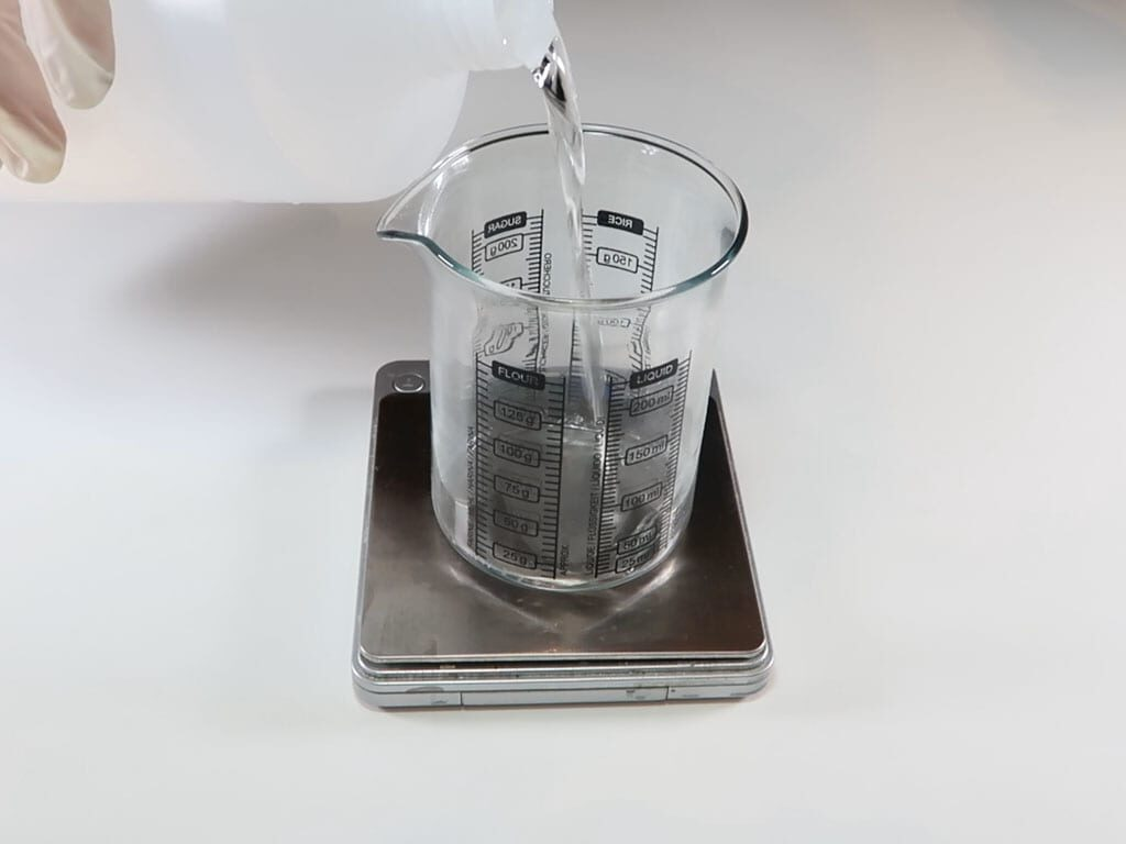 alcohol being added to a glass beaker sitting on digital scales