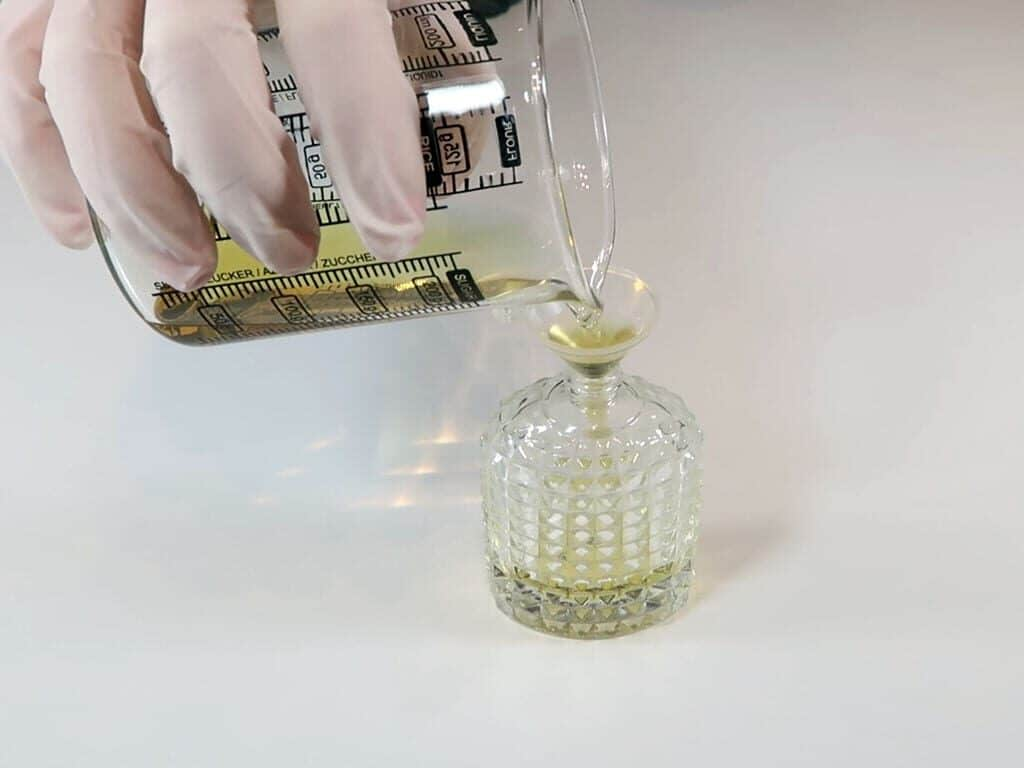 The perfume is poured into a 30ml glass perfume bottle, using a funnel