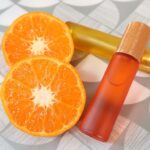 Two roll on perfumes sat next two halves of an orange