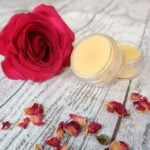 Two pots of homemade solid perfume with a rose and some rose petals around it
