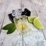 A 30ml bottle of cologne, sat next to another bottle, some lime segments and a couple of bay leaves