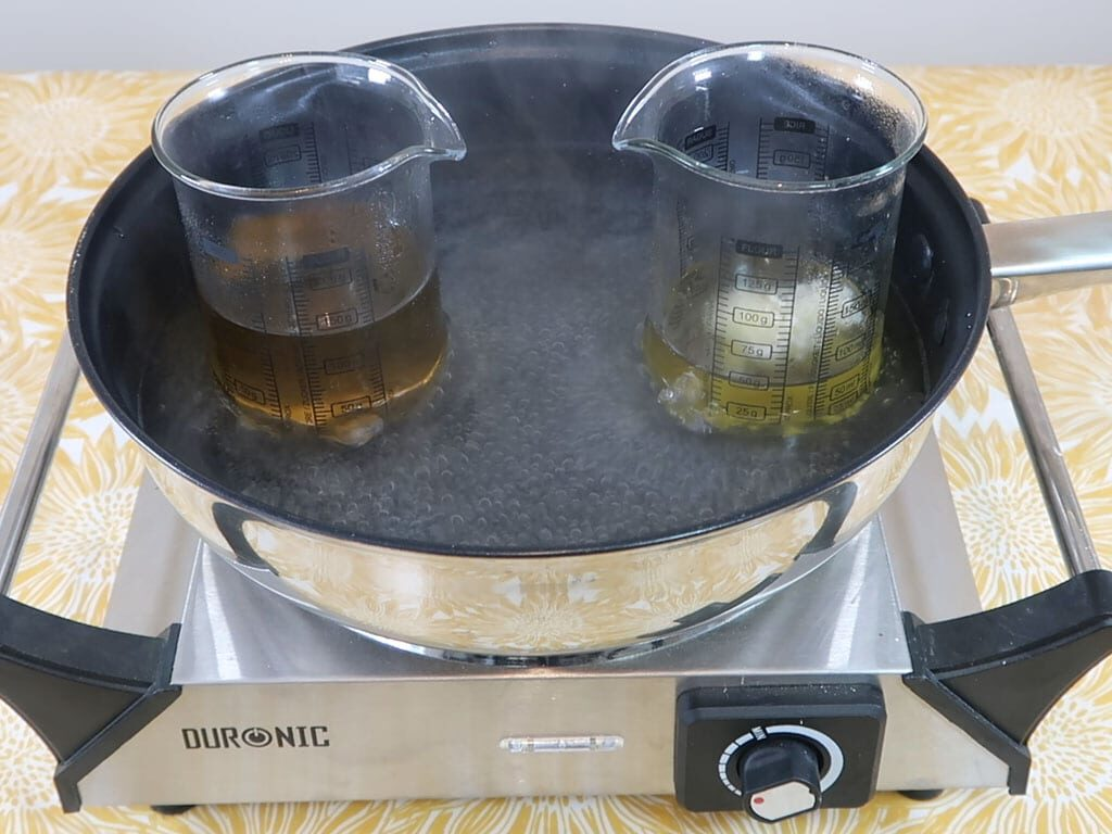 Oil and water phase beakers being heated in a water bath