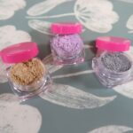 Three eye shadows sit together, all of different colors