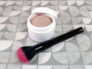 A pot of powdered foundation and a large application brush