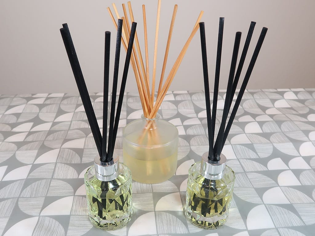 3 reed diffusers sit on a table