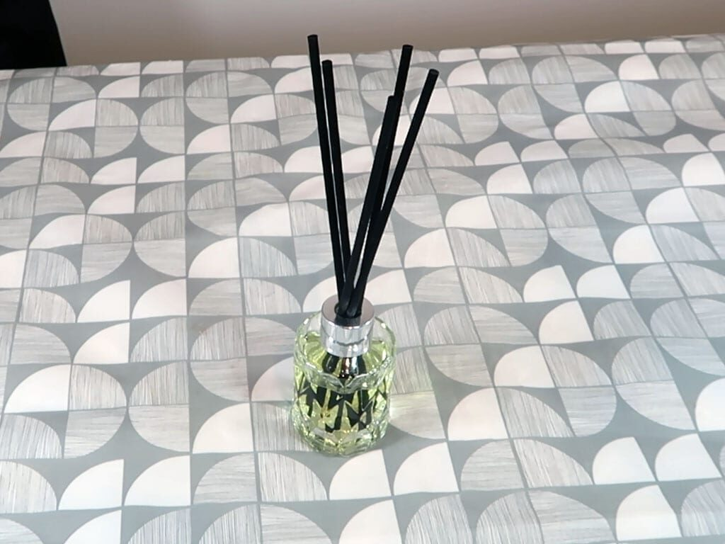 A reed diffuser sits on a table