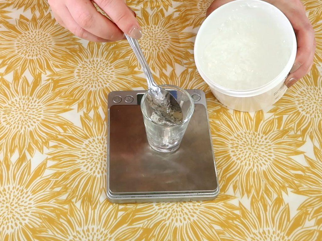 Aloe vera gel is measured in a small glass beaker