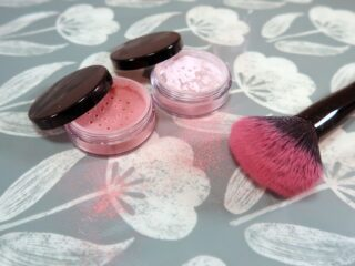 Two powdered blushes sit next to a blusher brush
