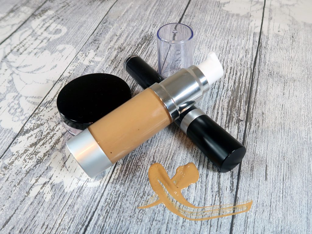 Liquid foundation sitting with a blush sifter and mascara tube