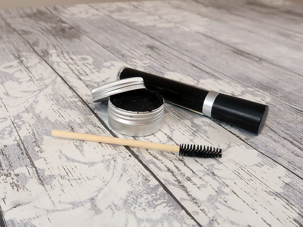 Two beautiful mascaras, one in a tube and the other in a pot, next to an applicator brush