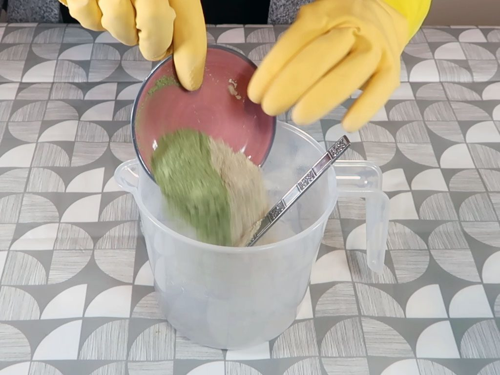 The wheatgrass and green clay are added to the liquid lye