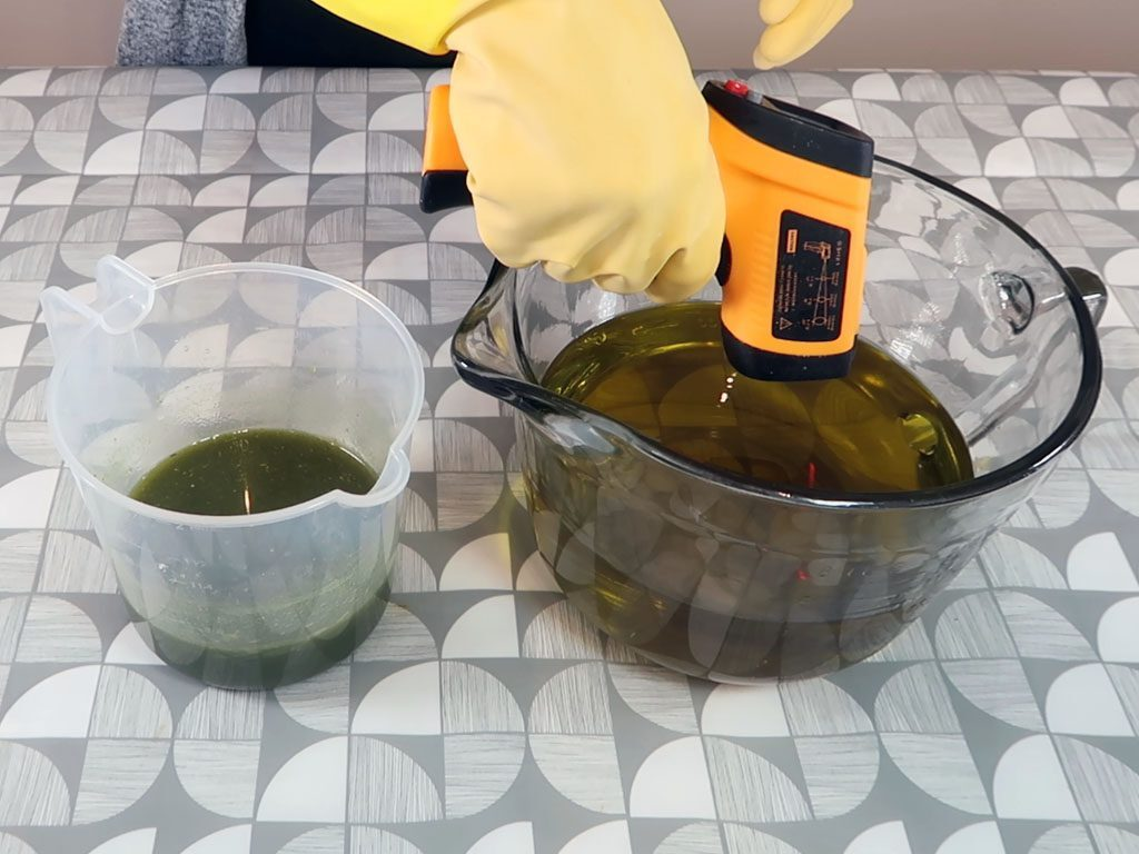 A soap maker measures the temperature of the oils to compare with the lye